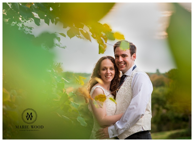 bride and groom in front of a tree in autumn with bright colours from the leaves