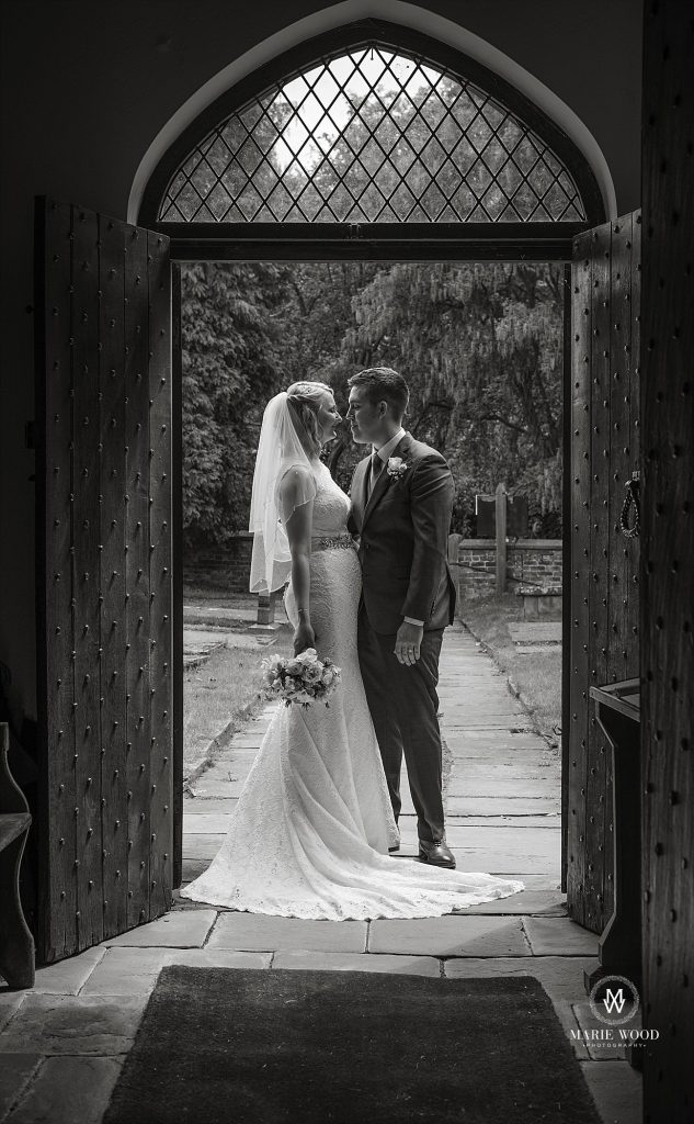 bride and groom in the door way of st lawrence church in Over Peover