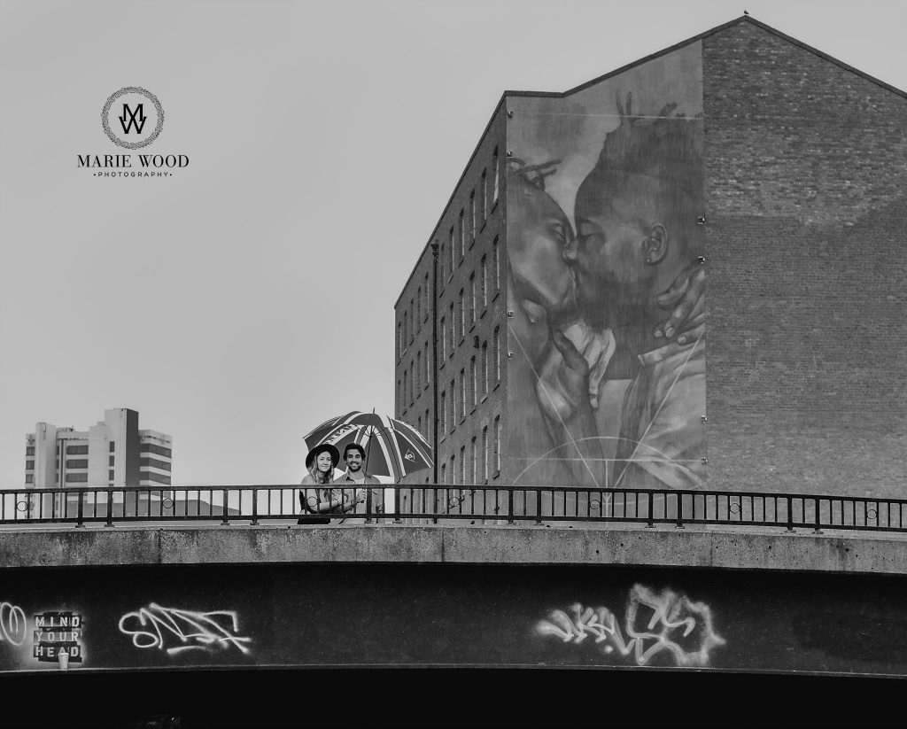 couple being shot infront of the graffiti on a wall in manchester