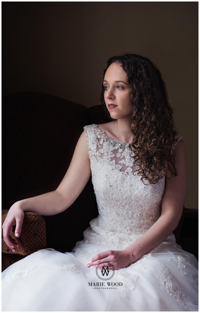 bride sat by the window in her wedding dress from esme