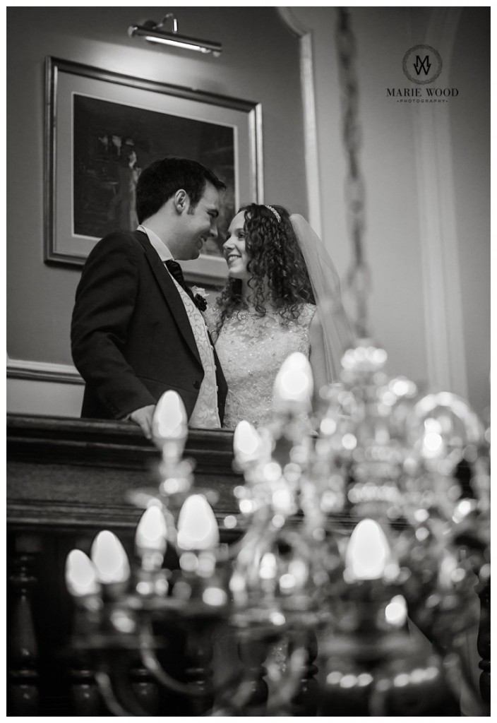 bride and groom stood on a landing in the dukenhalgh hotel in front of a chandelier