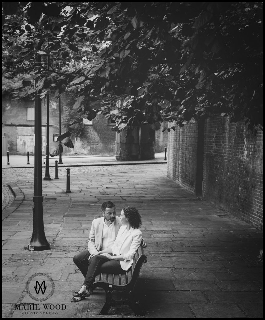 couple sat on a bench in castlefield manchester having a photoshoot